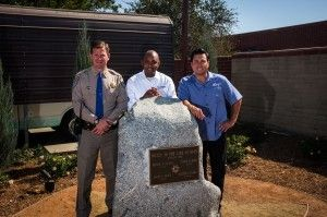 (From left) CHP Capt. Ed Krusey; Curtis Woods, general manager of Eternal Valley Memorial Park and Mortuary; and Chris Angelo, CEO of Stay Green Inc., pose for a photo at a memorial for four CHP officers killed in the 1970 shootout known as the Newhall Incident. The memorial is located outside the CHP's Newhall Area Station and was completed through a partnership between Stay Green and Eternal Valley.